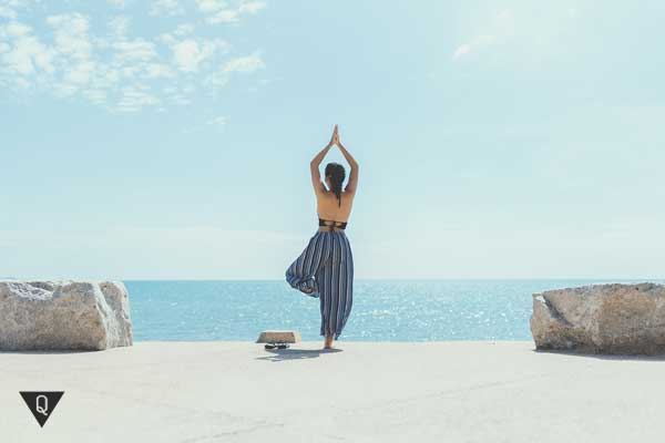 Девушка медитирует на берегу моря