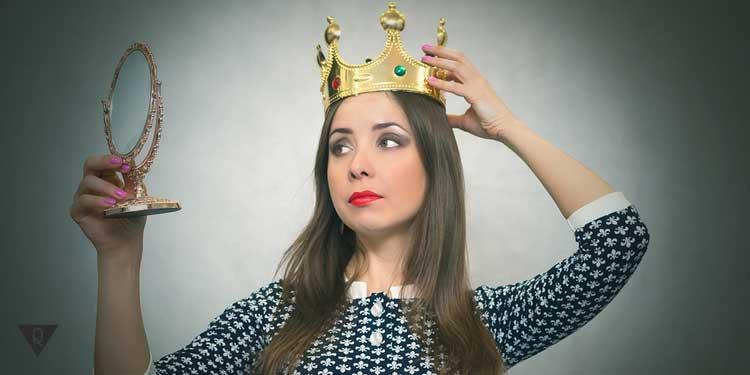 Девушка в короне смотрит в зеркало, как символ того, что она проявляет эгоизм в отношениях.