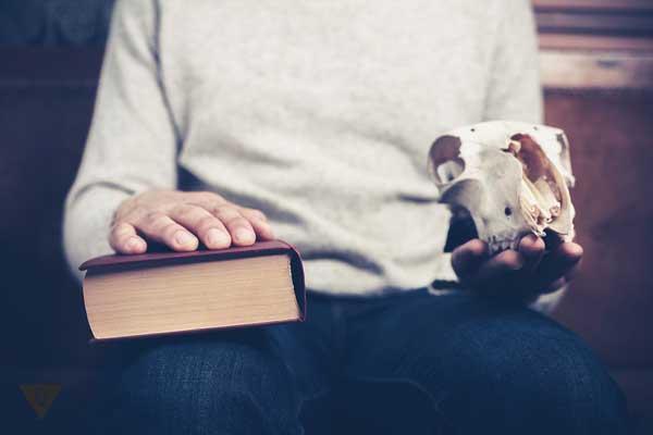 Мужчина с книгой и черепом в руках