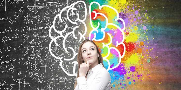 Девушка возле доски, где нарисован мозг с формулами и раскрашен яркими цветами, как символ наличия эмоционального интеллекта