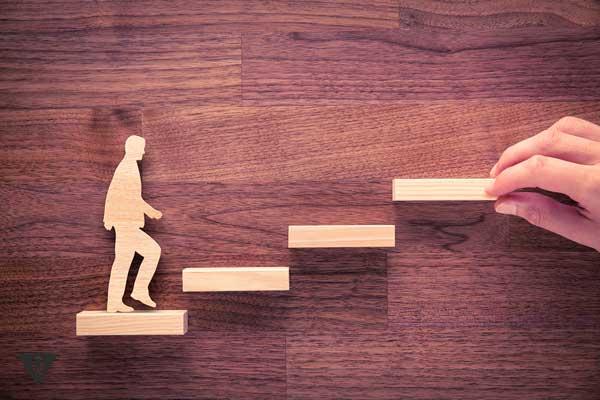 Деревянный человечек поднимается по ступенькам, как символ его саморазвития