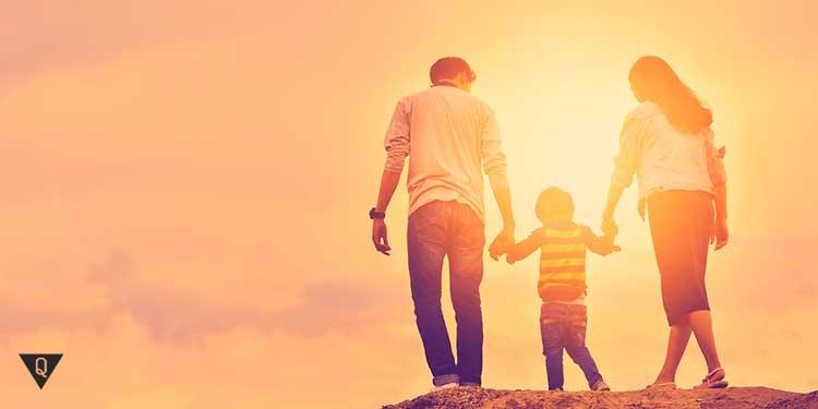 Родители гуляют с ребенком на закате солнца
