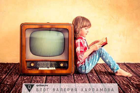 ребенок читает книгу у телевизора