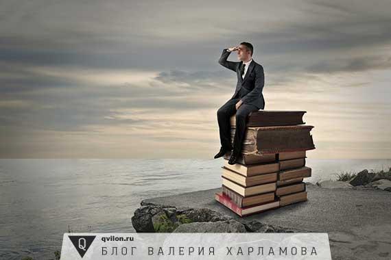 человек сидит на книгах и смотрит вдаль