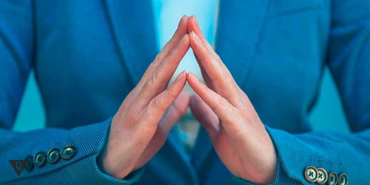 девушка в пиджаке держит руки пирамидой