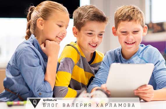 ребенок показывает друзьям планшет