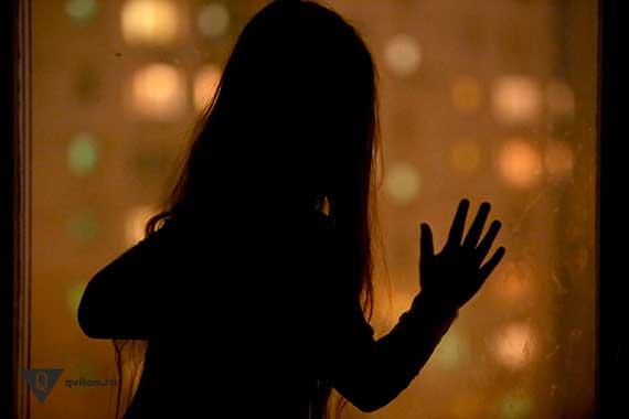 девушка в темноте стоит у окна