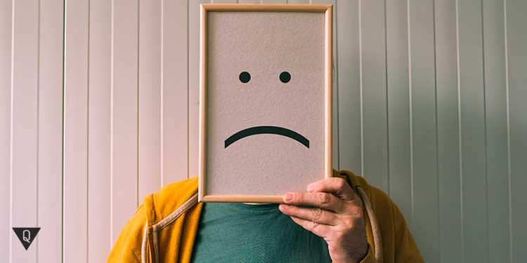 человек держит рамку перед лицом, с печальной улыбкой