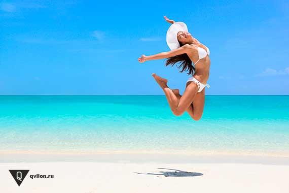 девушка прыгает от радости на берегу океана