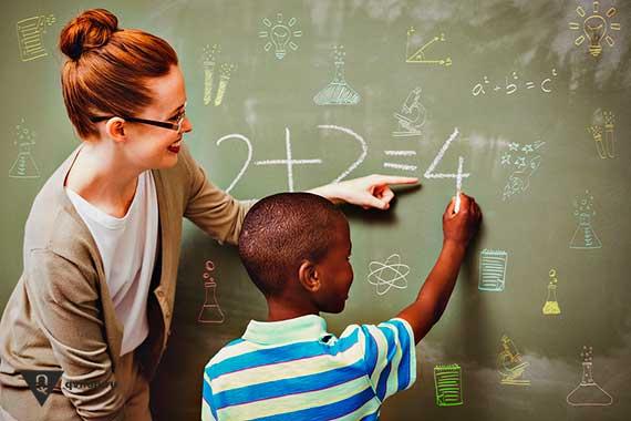 мальчик на доске решает пример с учительницей