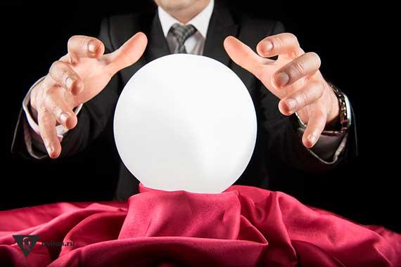 мужчина в костюме держит руки над магическим шаром