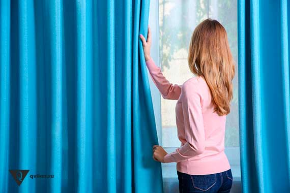 девушка закрывает шторы