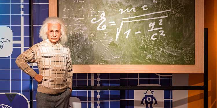 Альберт Эйнштейн на фоне доски с формулой