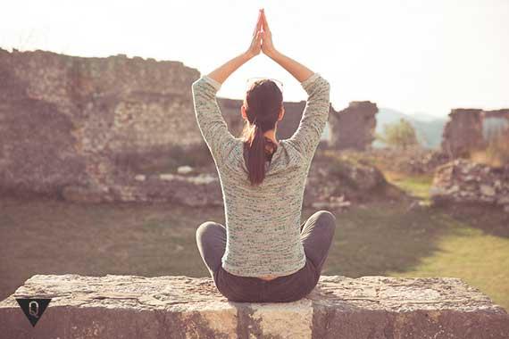 девушка медитирует на фоне древних развалин