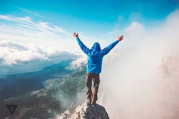 человек стоит на вершине горы