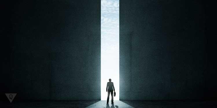 человек стоит перед приоткрытими высокими вратами