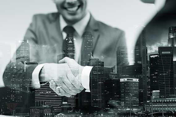 бизнесмены жмут руки на фоне мегаполиса