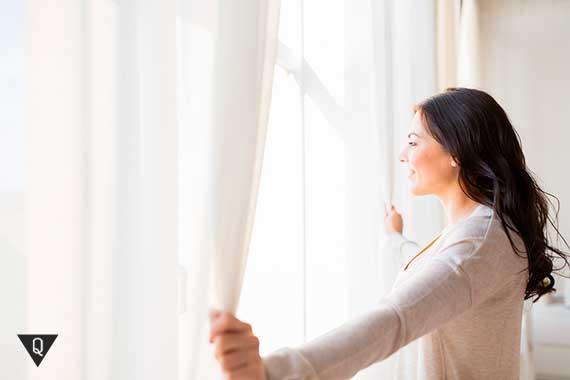 радостная девушка смотрит в окно