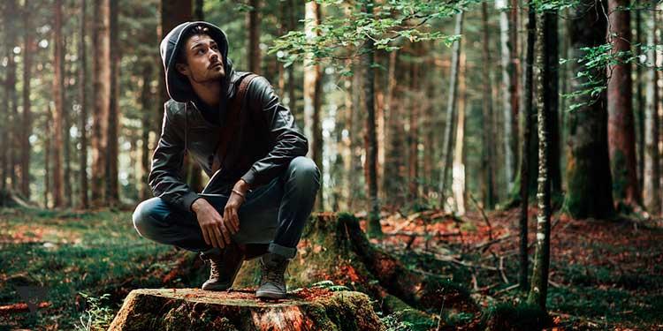 Мужчина сидит на пне в лесу