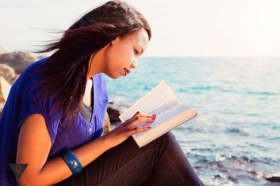 девушка читает книгу на берегу моря