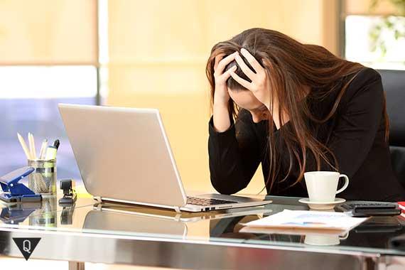 девушка держится за голову на рабочем месте