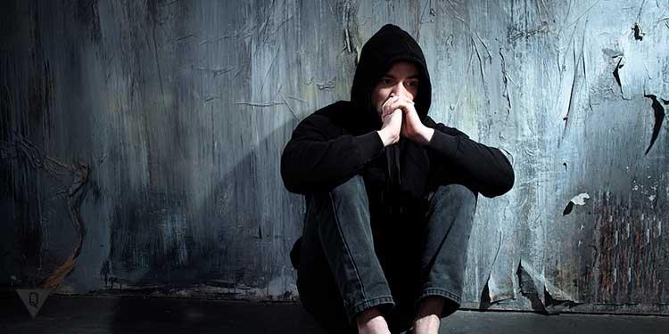 человек в капюшоне сидит в темном углу