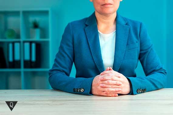 уверенная женщина сидит за столом