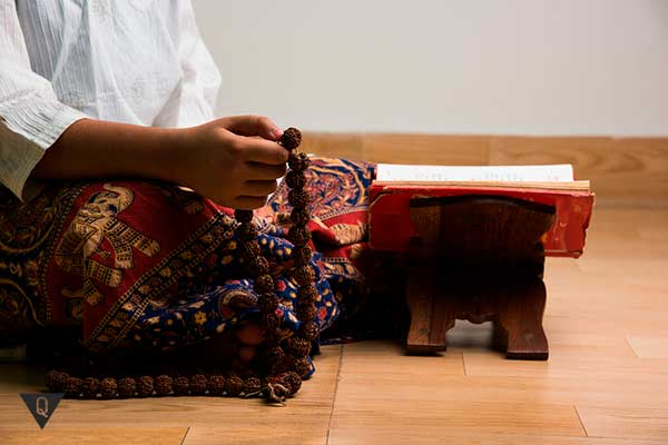 человек медитирует с чётками