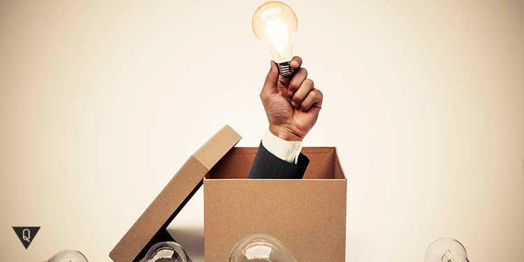 рука достает из коробки горящую лампочку