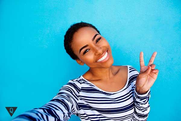 темнокожая девушка показывает знак мира