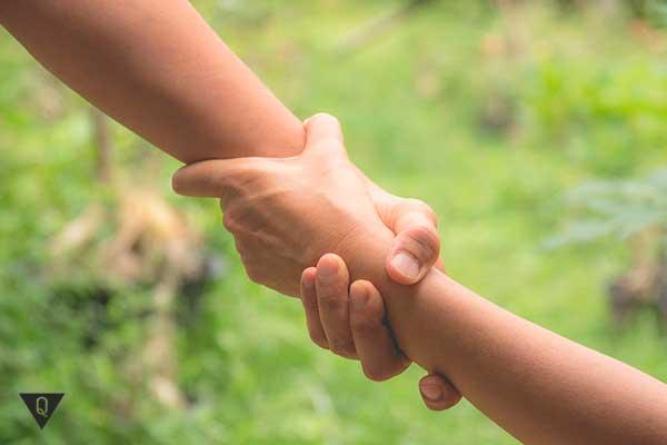 человек помогает другому взяв за руку