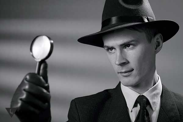мужчина в черной шляпе и с лупой