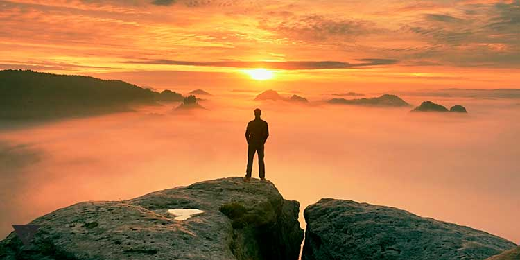 человек стоит на горе на фоне красивого заката