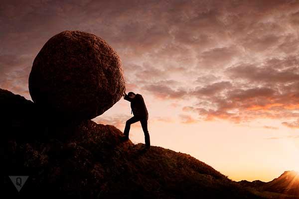 мужчина двигает камень в гору