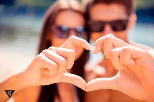 мужчина с девушкой показывают знак любви