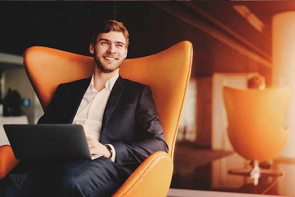 мужчина с ноутбуком сидит в кресле