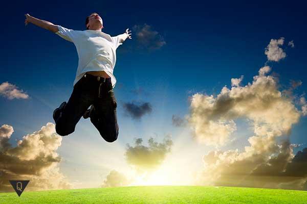 счастливый мужчина прыгает на зеленом поле