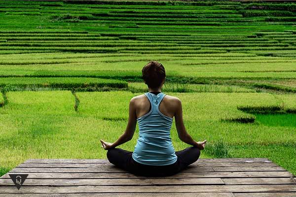 девушка медитирует на фоне поля
