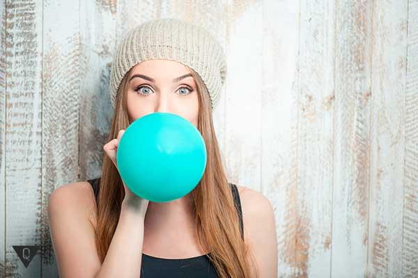 девушка надувает воздушный шарик