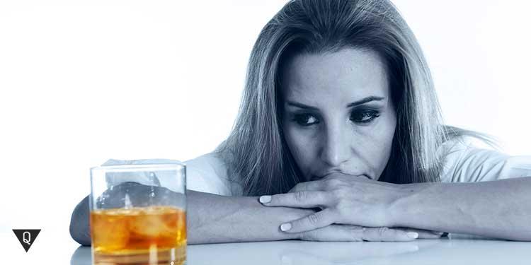 женщина смотрит на стакан с алкогольным напитком