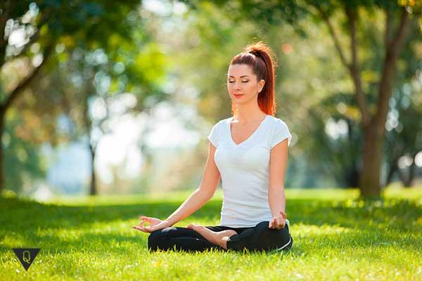 девушка медитирует на зеленой поляне