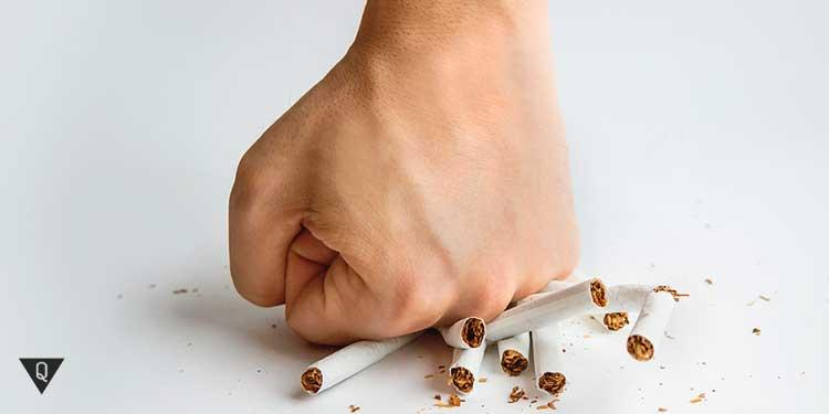 мужчина ломает кулаком сигареты