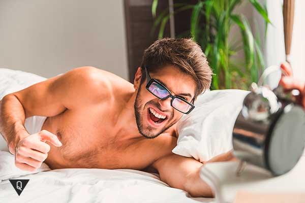 мужчина смотрит на будильник