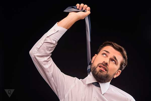 мужчина вешает себя галстуком