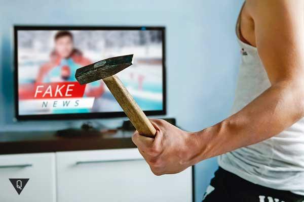 мужчина с молотком бросается на телевизор