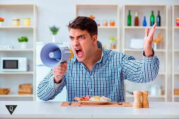 мужчина кричит в рупор за столом