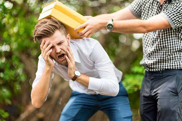 мужчина бьет по голове учебниками другого мужчину