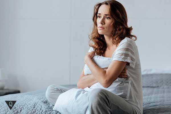женщина сидит расстроенная в кровати