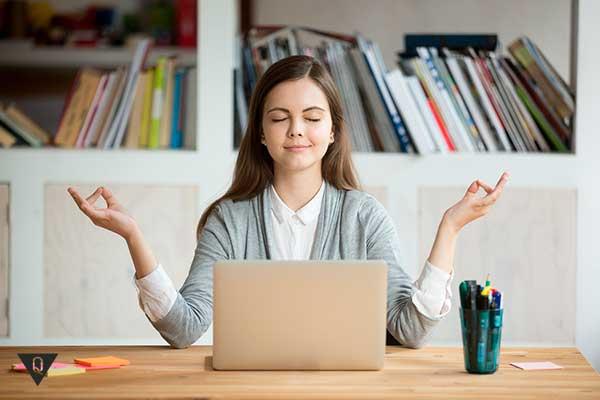 девушка медитирует около компьютера
