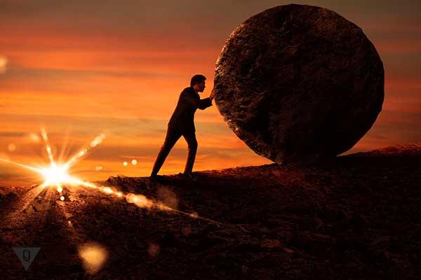 Мужчина толкает камень в гору на закате